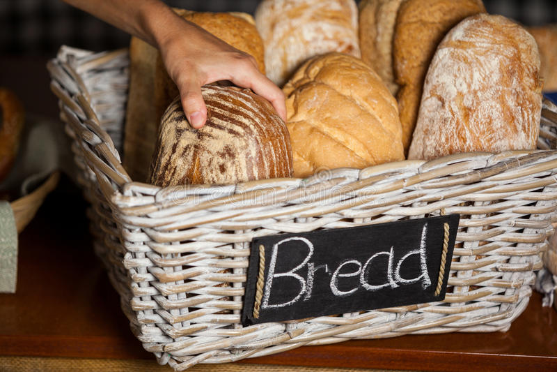 拿着面包的女职工在柜台在面包店商店 库存照片