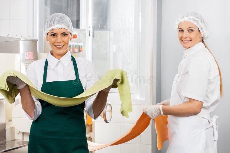 拿着面团板料的愉快的女性厨师在厨房 图库摄影