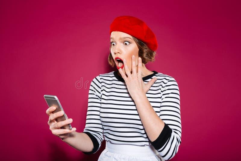 拿着面颊的震惊姜妇女,当使用智能手机时 库存图片