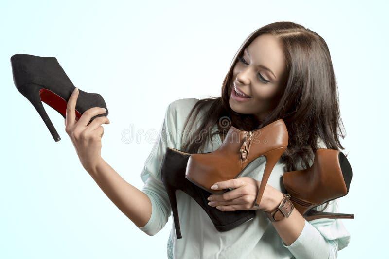 拿着鞋子分类的时尚女孩 免版税图库摄影