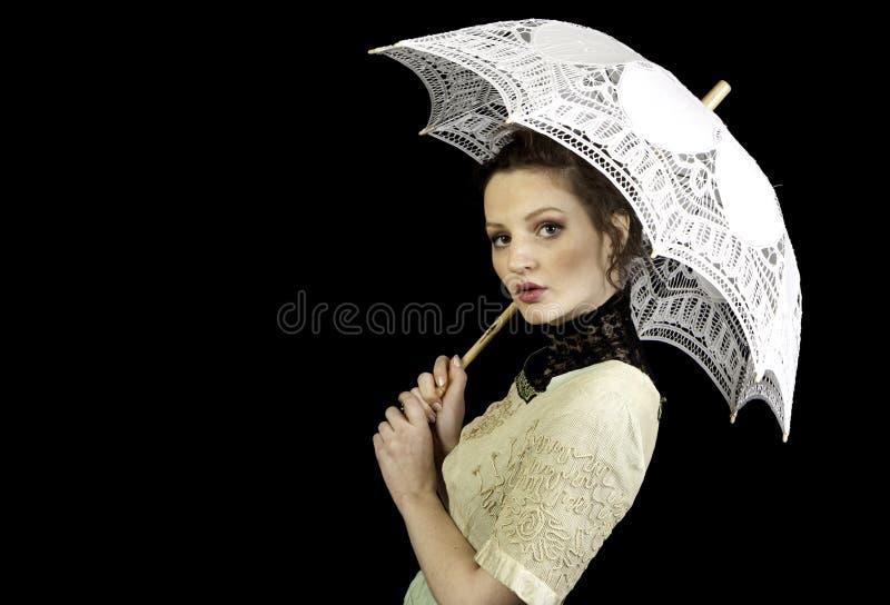 拿着鞋带伞的维多利亚女王时代的礼服的女孩 免版税库存图片