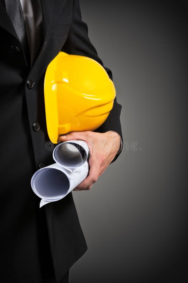 拿着项目文件和盔甲的建筑工人的手 免版税图库摄影