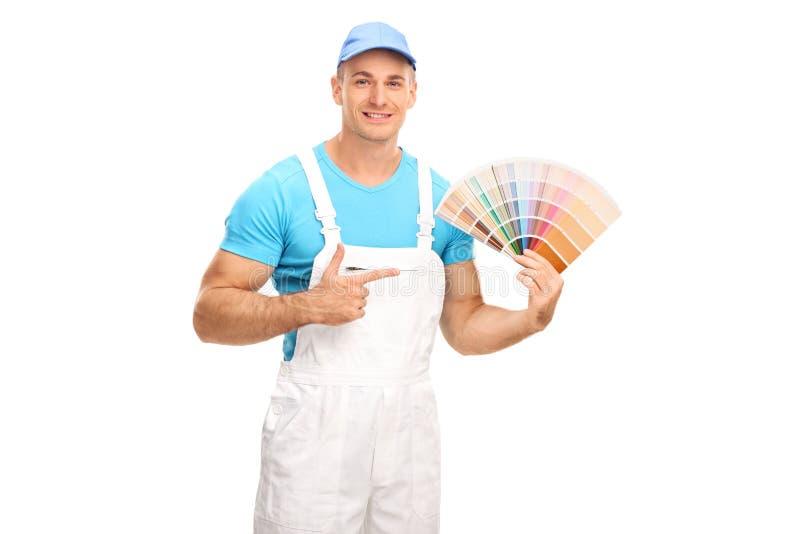 拿着颜色样片和指向它的画家 免版税图库摄影