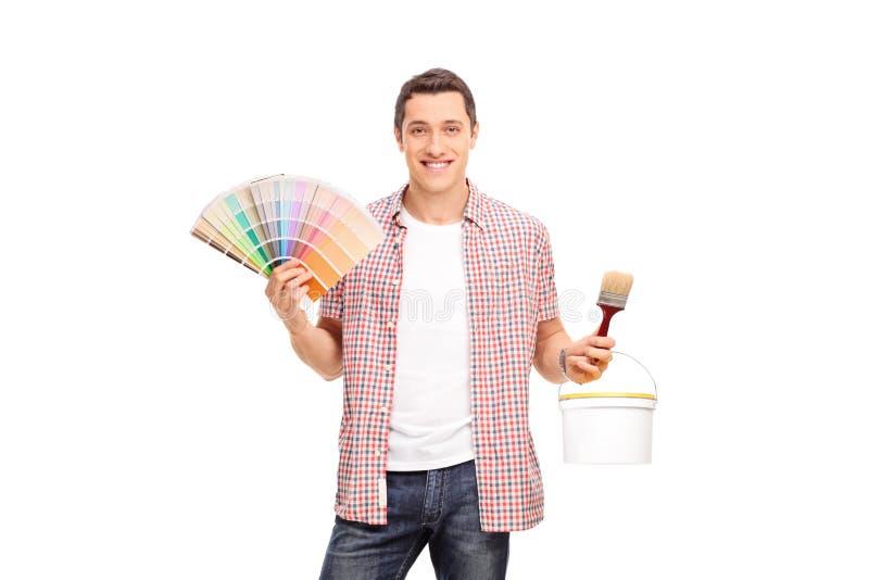 拿着颜色样片和油漆刷的年轻人 免版税图库摄影