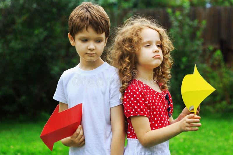 拿着颜色箭头的孩子指向右和左,在夏天 库存照片