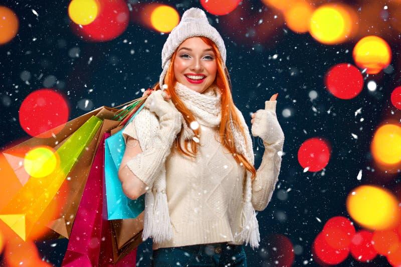 拿着颜色袋子和在与雪的冬天背景和光的购物妇女在黑星期五、圣诞节和新年 库存照片