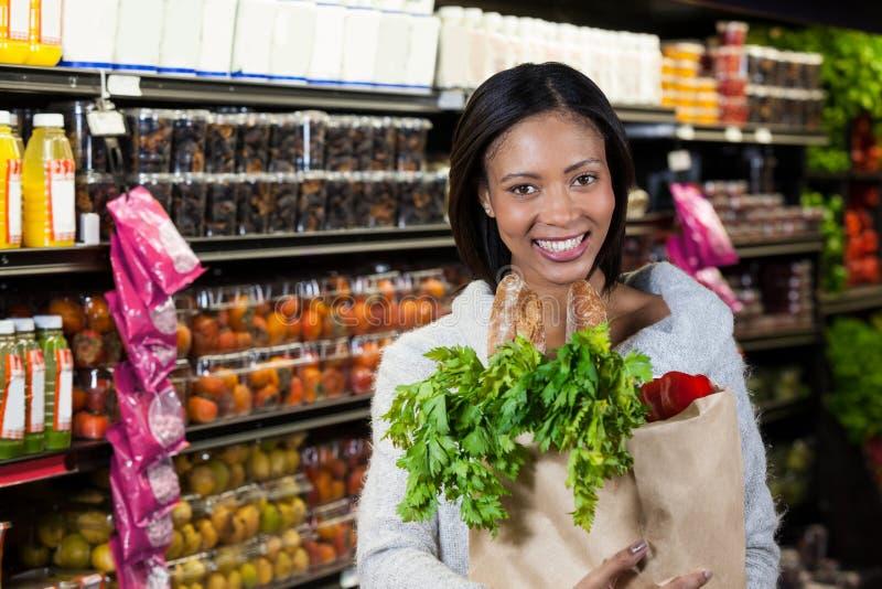 拿着食品杂货袋的微笑的妇女画象 免版税图库摄影