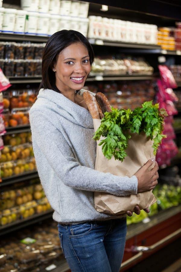 拿着食品杂货袋的微笑的妇女画象 免版税库存图片