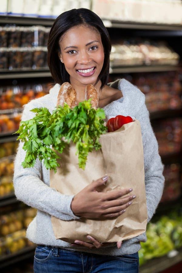 拿着食品杂货袋的微笑的妇女画象 图库摄影