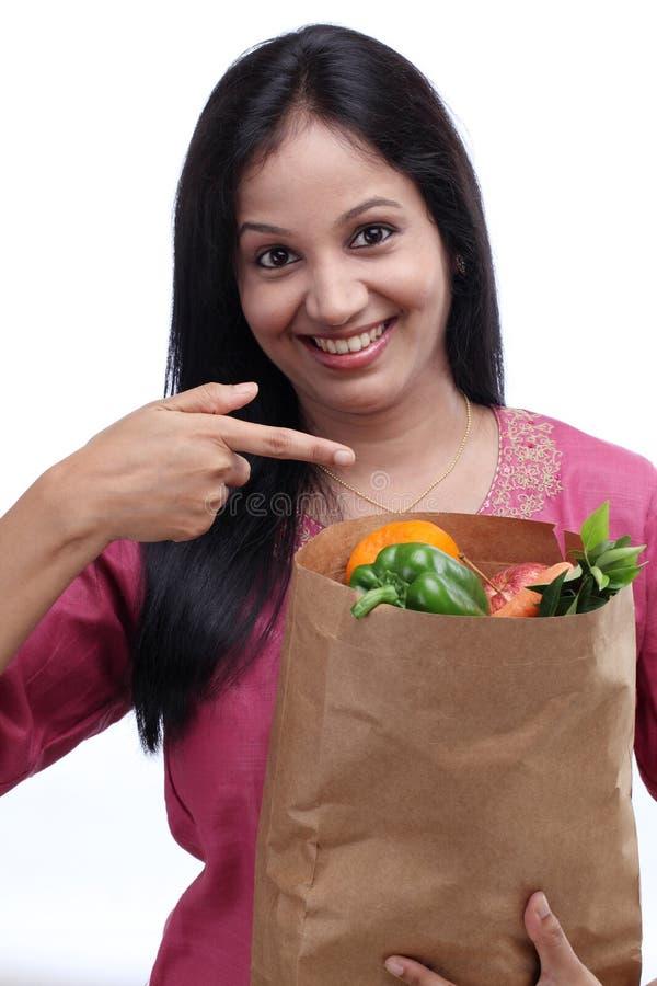 拿着食品杂货袋的年轻印地安女孩 库存照片