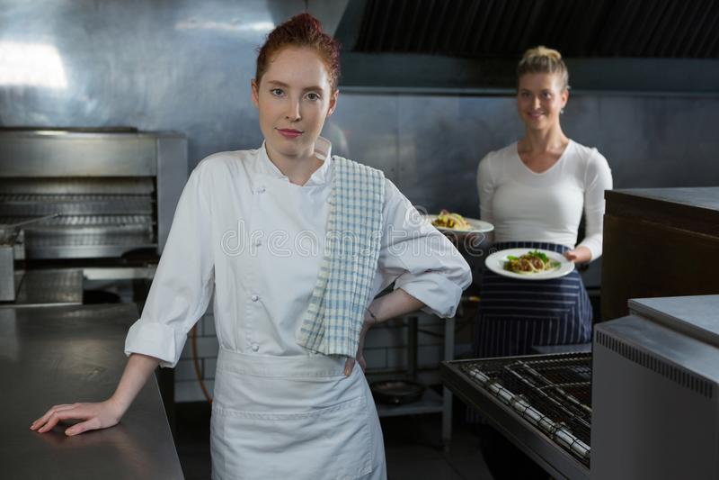拿着食物板材的女性厨师 库存图片