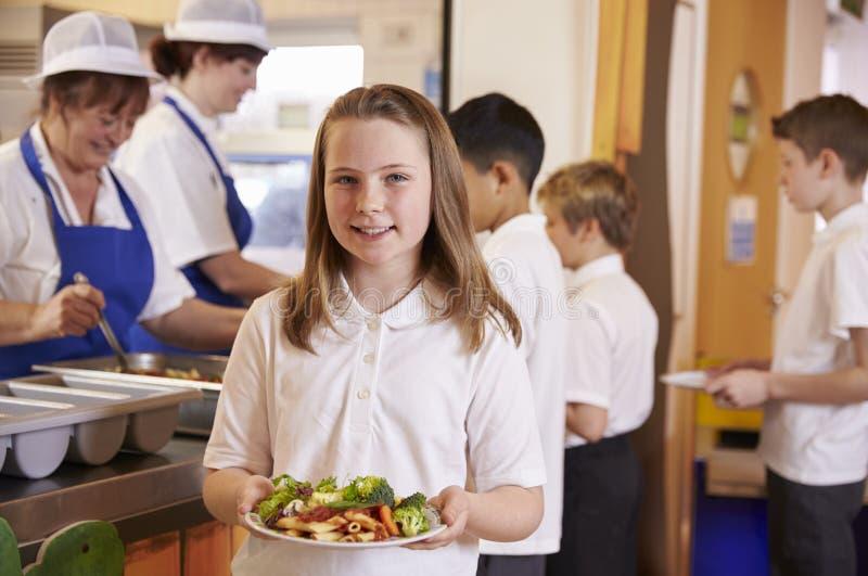 拿着食物的板材女小学生在学校食堂 免版税库存照片