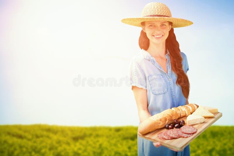 拿着食物盘子的微笑的妇女的综合图象 库存照片
