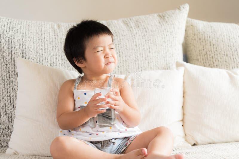 拿着饮用水的愉快的矮小的亚洲女孩手玻璃 库存图片