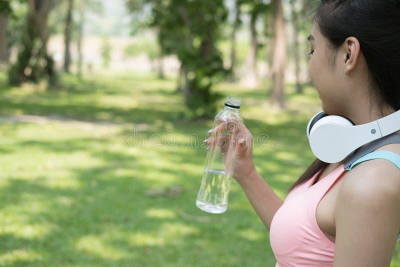 拿着饮用的wat的年轻美丽的亚裔健身运动员妇女 免版税库存图片