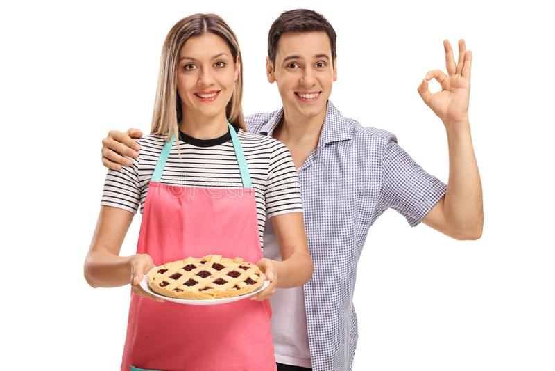 拿着饼和年轻人的妇女做好标志 库存图片