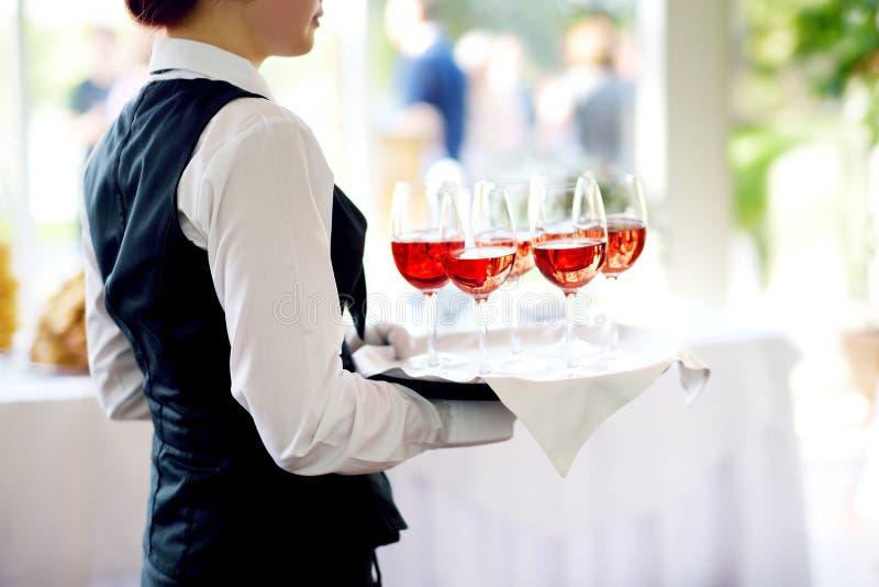 拿着香槟和酒杯的盘女服务员在欢乐事件 免版税库存图片