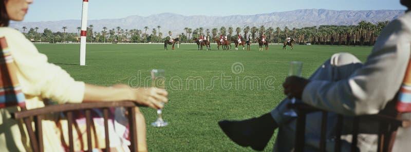 拿着香槟槽的夫妇,当观看马球比赛时 免版税库存照片