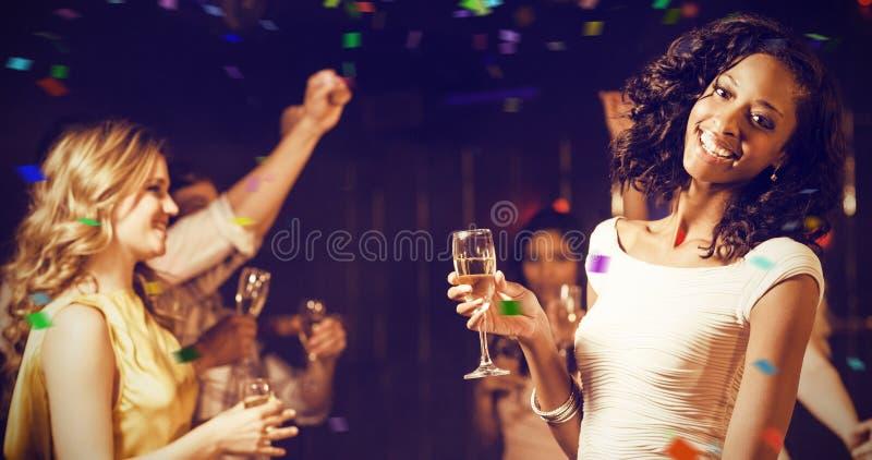 拿着香槟槽的愉快的朋友的综合图象,当跳舞时 库存图片