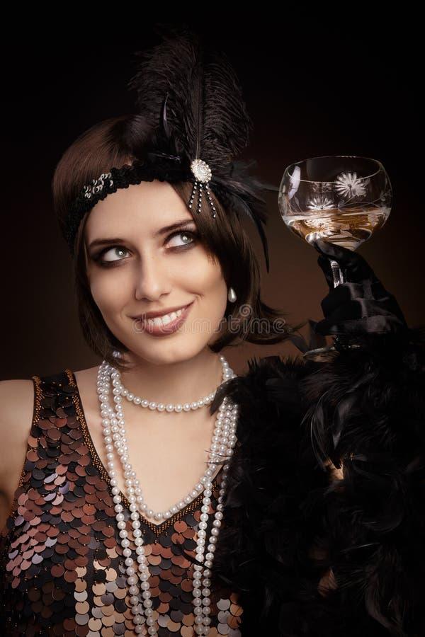 拿着香槟的减速火箭的20s样式妇女玻璃 免版税库存图片