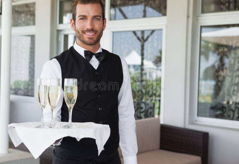 拿着香槟的盘子英俊的微笑的侍者 图库摄影