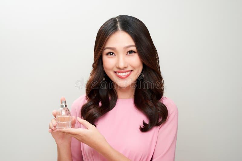 拿着香水瓶和应用它的美丽的亚裔妇女 免版税库存照片