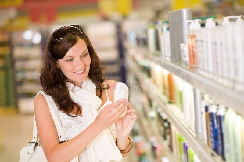 拿着香波购物微笑的妇女的化妆用品 库存照片