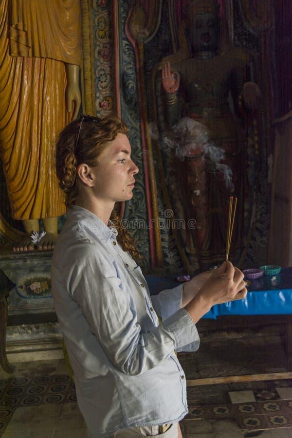 拿着香火的灼烧的棍子俏丽的女孩在圣洁佛教寺庙 图库摄影