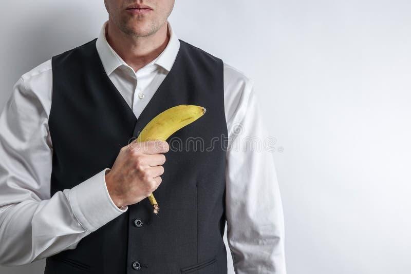 拿着香蕉的穿着体面的人喜欢枪 库存照片