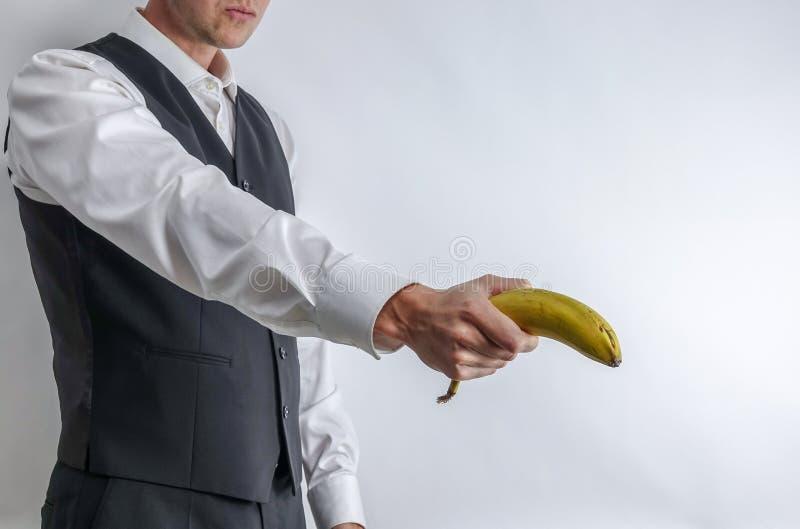 拿着香蕉的衣服背心的穿着体面的人喜欢枪 库存照片