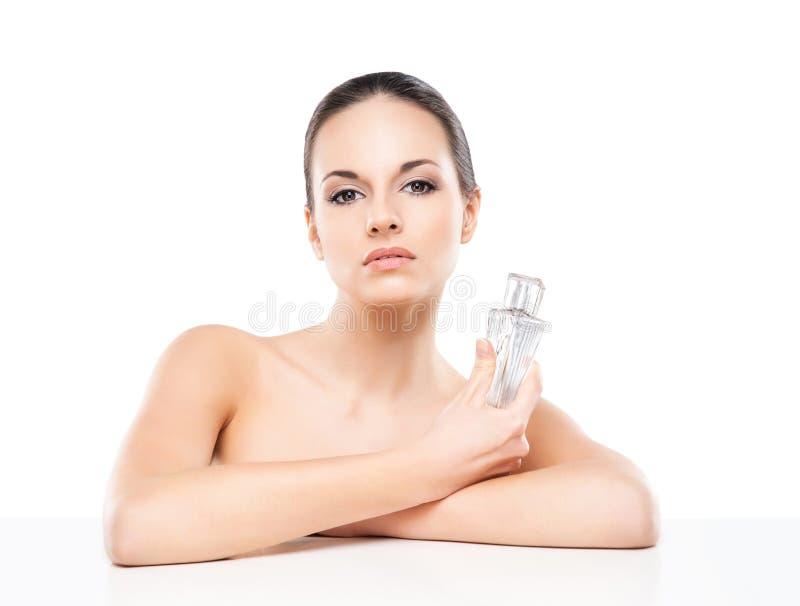 拿着香水的一名年轻赤裸妇女的画象被隔绝在白色 免版税图库摄影