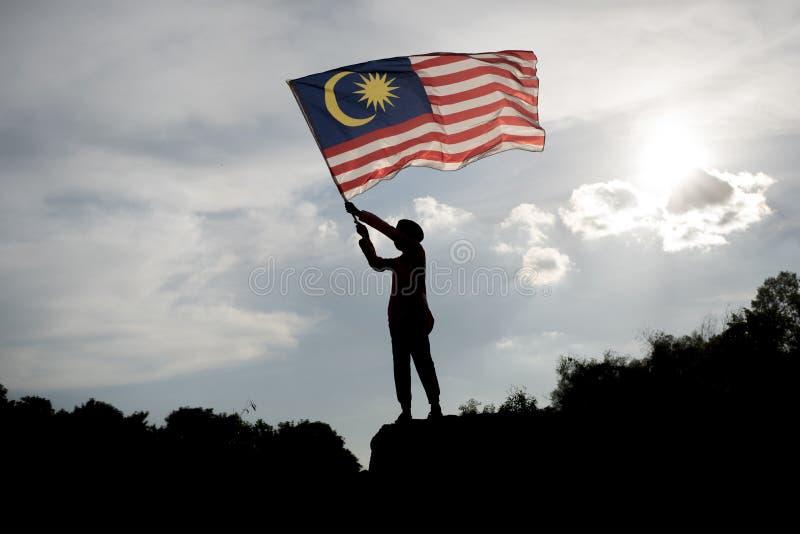 拿着马来西亚旗子的男孩的剪影庆祝马来西亚独立日 库存照片