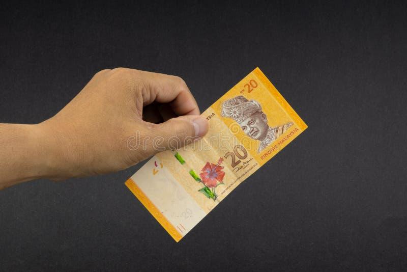 拿着马来西亚林吉特MYR货币钞票的手 免版税库存照片