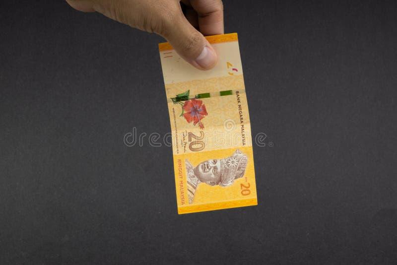 拿着马来西亚林吉特MYR货币钞票的手 库存照片