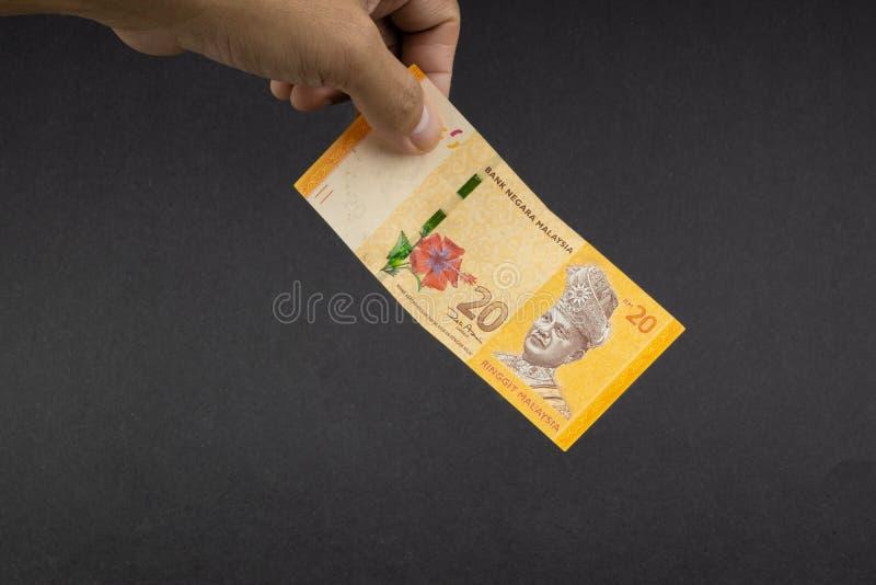 拿着马来西亚林吉特MYR货币钞票的手 免版税库存图片