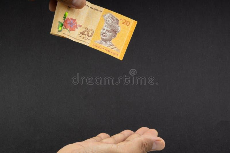 拿着马来西亚林吉特MYR货币钞票的手 库存图片
