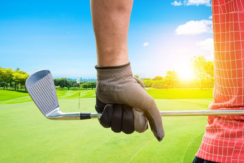 拿着高尔夫俱乐部的高尔夫球运动员由手套手对准备在与阳光光芒的高尔夫球赛 免版税库存照片