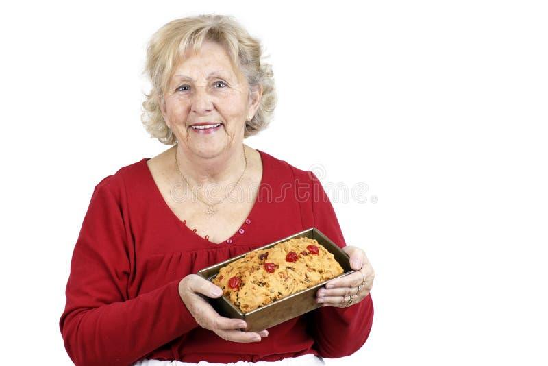 拿着高级妇女的蛋糕果子 免版税库存照片