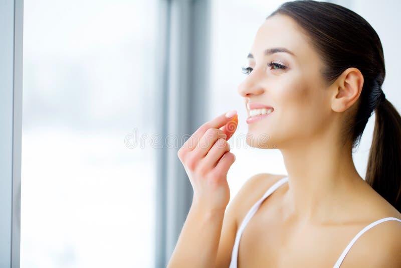 拿着鱼油药片的美丽的妇女手中 健康营养 免版税库存图片