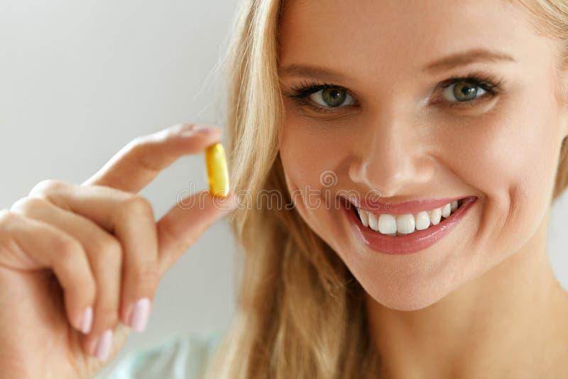 拿着鱼油药片的美丽的妇女手中 健康营养 图库摄影