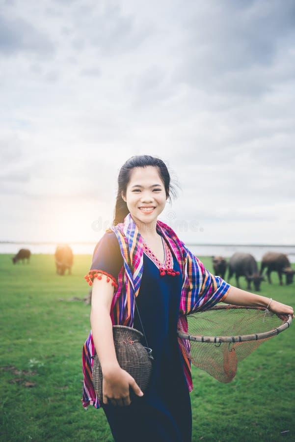 拿着鱼陷井和篮子的美丽的亚裔女孩,准备抓走在领域的鱼在湖附近 免版税图库摄影