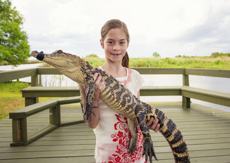 拿着鳄鱼的逗人喜爱的女孩在佛罗里达沼泽地附近 库存照片