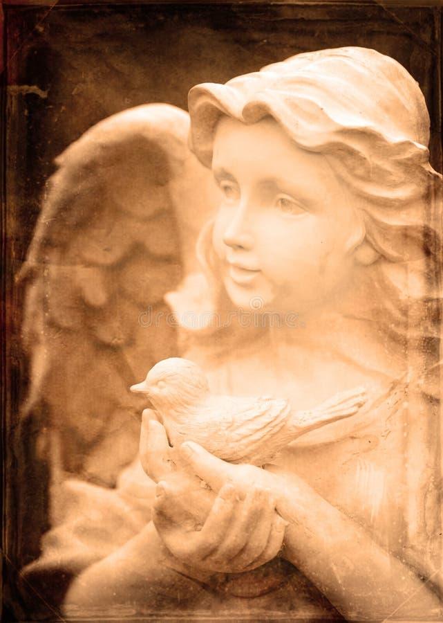 拿着鸟的天使雕象 库存图片
