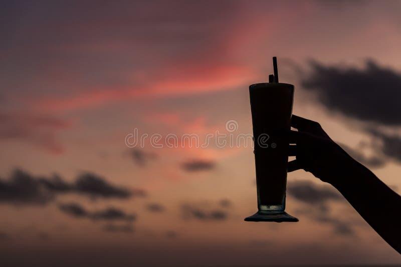 拿着鸡尾酒的妇女的手反对日落 快乐时光 库存照片