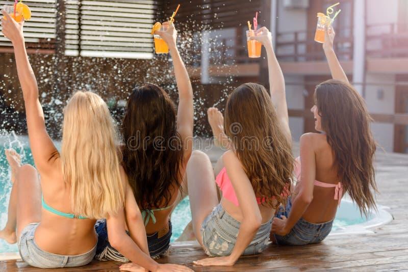 拿着鸡尾酒的泳装的四名妇女在游泳池 免版税库存图片