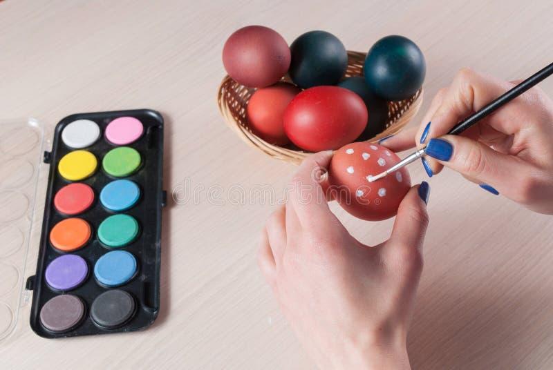 拿着鸡蛋和绘它与刷子的妇女特写镜头照片 免版税图库摄影