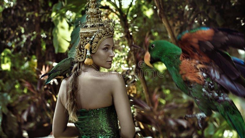 拿着鹦鹉的亚裔女王/王后 免版税库存图片