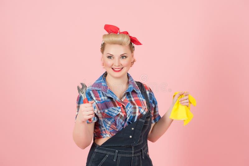 拿着黄色乳汁手套和板钳的画报样式的白肤金发的愉快的微笑的女性隔绝在淡色桃红色背景 图库摄影