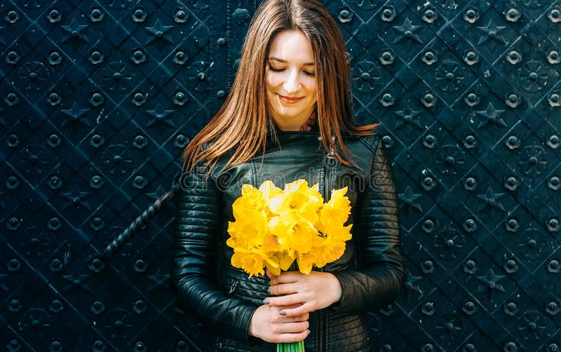 拿着黄色春天花的一名年轻深色的妇女的画象 库存照片