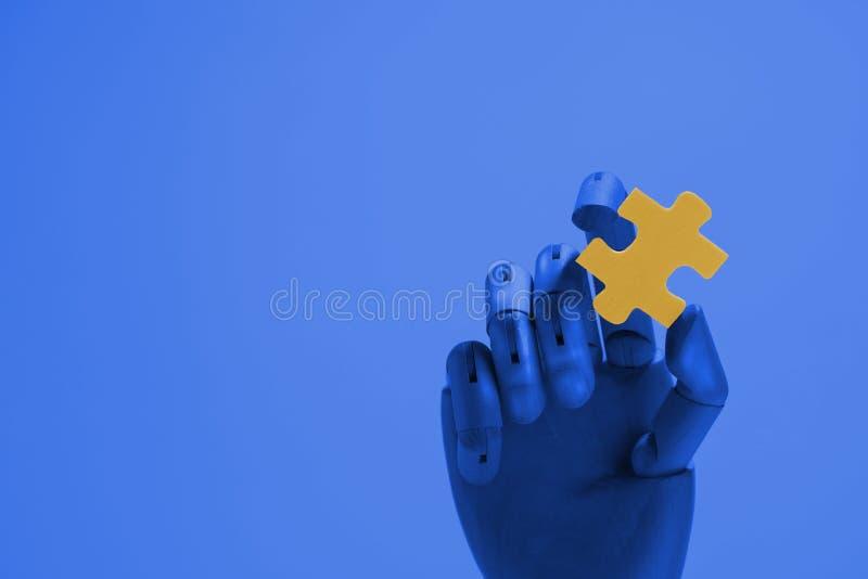 拿着黄色曲线锯的片断的机器人手 免版税图库摄影